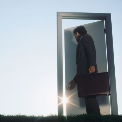 Businessman opening metaphorical door in field